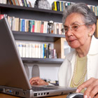 Elderly woman sitting at a laptop.